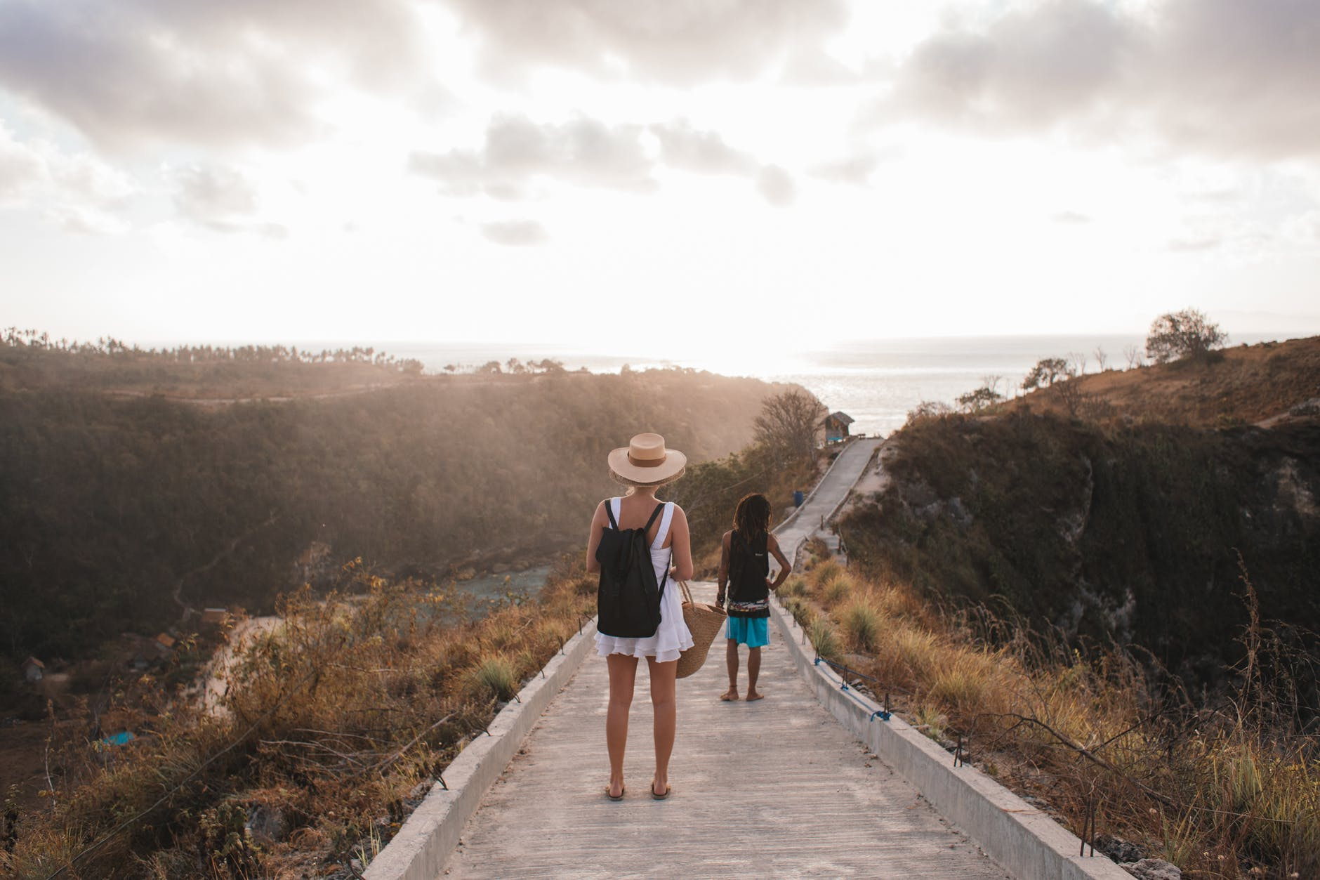 unrecognizable mother with daughter contemplating shiny sky from walkway