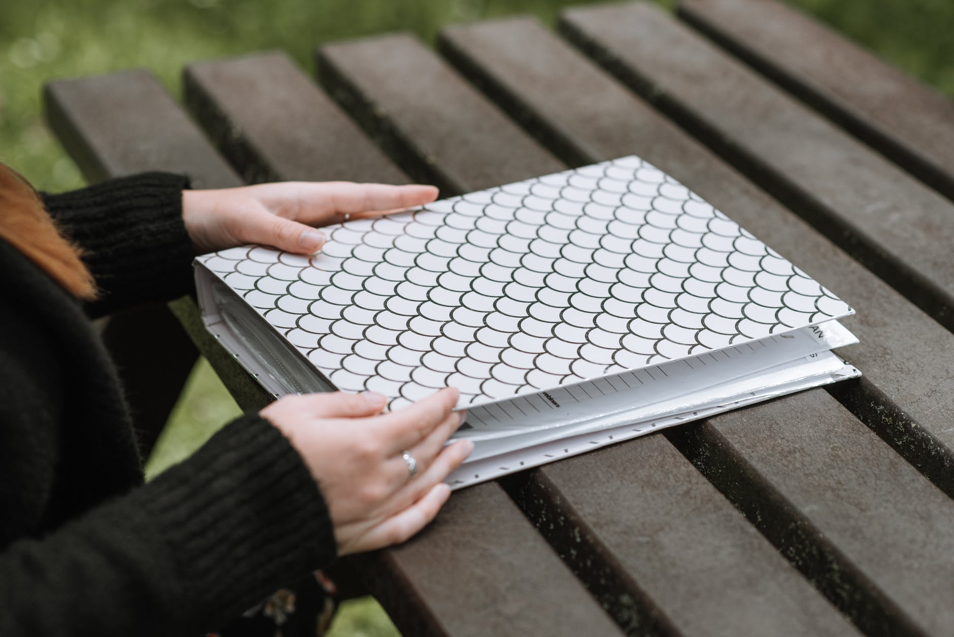 woman with folder in patterns on bench