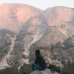 anonymous hiker recreating on rocky cliff and enjoying mountain view at sundown