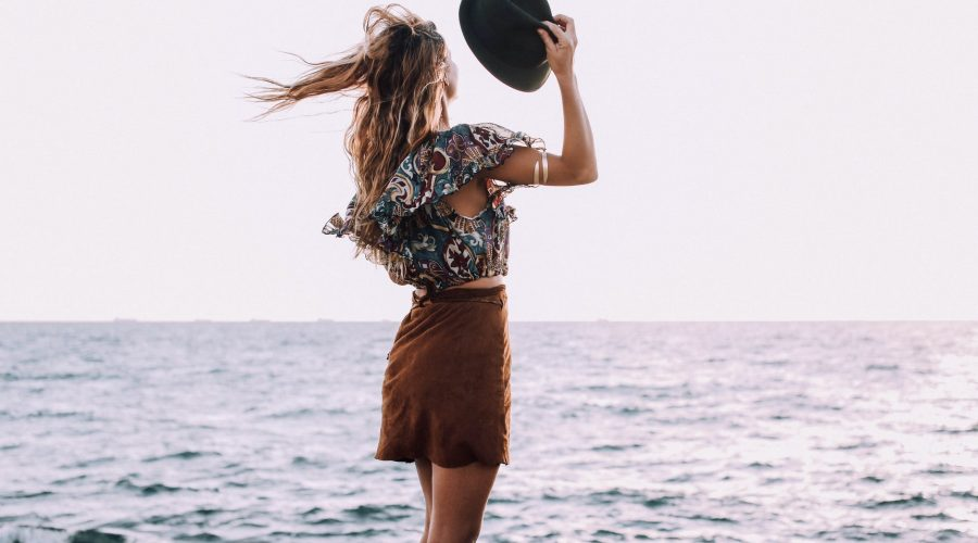 stylish female standing against ocean in windy day