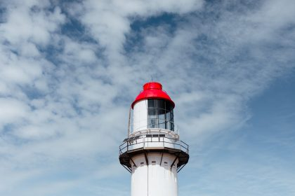 bright aged lighthouse under cloudy sky in daytime
