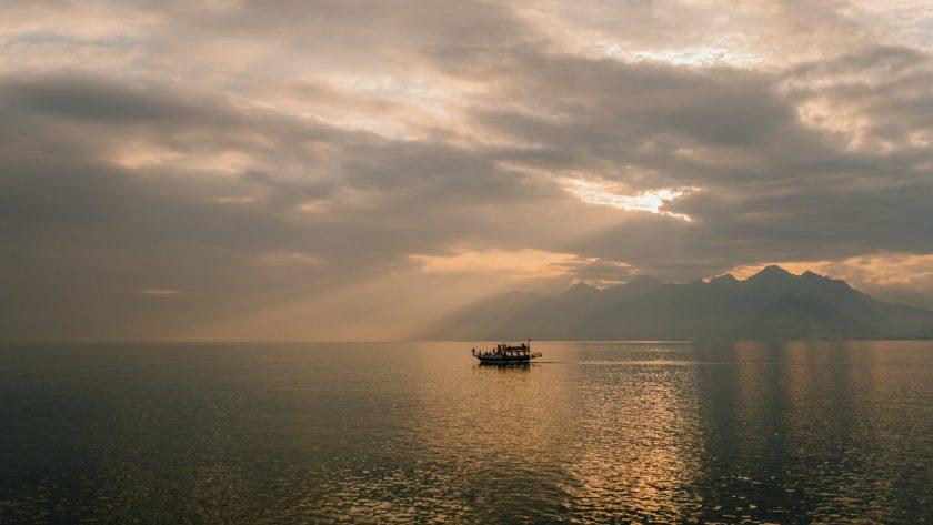 ship sailing on sea under sundown sky