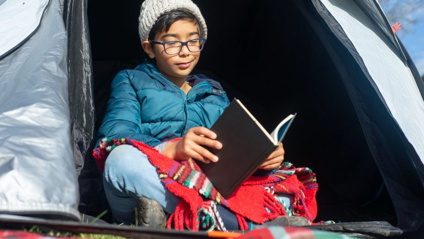 boy reading inside the tent