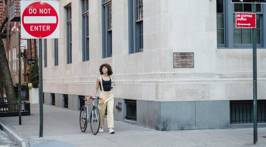 contemplative ethnic woman with coffee and bike walking on pavement
